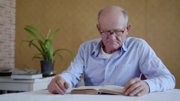 Thumbnail for Care for Elderly, Elderly Man with Glasses for Sight Loving Grandson Brings Water While Reading Book