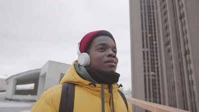 Young Man with Earphones in Urban Area