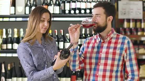 Thumbnail for Porträt von zuversichtlich jungen kaukasischen Mann Verkostung Rotwein aus Glas als lächelnd Brünette Frau
