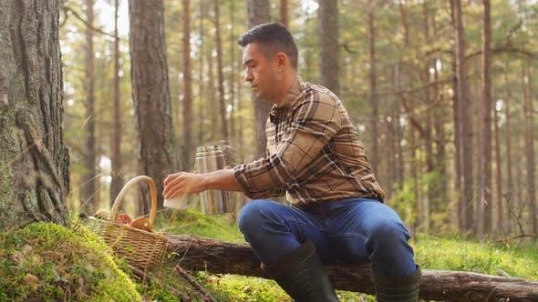 Mann mit Pilzkorb Getränke Tee im Wald