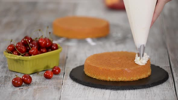 Thumbnail for Decorating a Cherry Cake with Cream From the Pastry Bag.