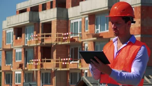 Thumbnail for Travailleur de la construction travaille sur la tablette devant le chantier de construction