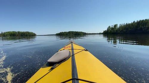 Sailing on Yellow Kayak Along Tranquil Dark Blue Lake Water