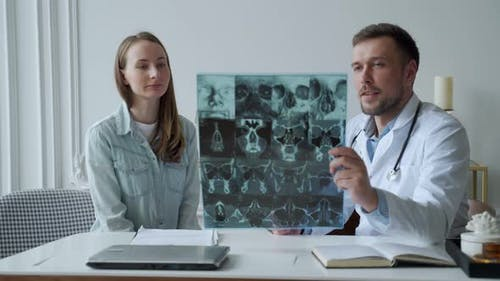 Man Doctor Show Xray Result and Explain of Health Problem to Women Patient in His Office