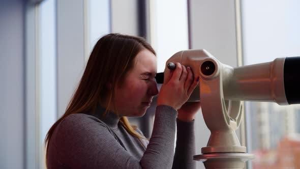 Young woman looks through stationary binoculars