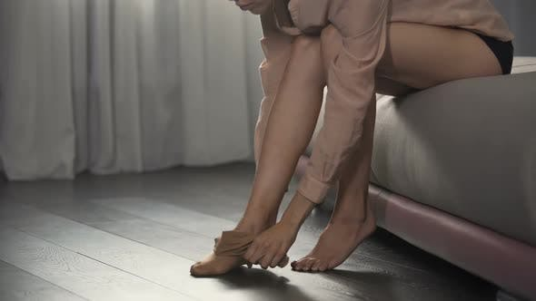 Thumbnail for Girl dressing pantyhose on her slender legs sitting in bedroom, going to work