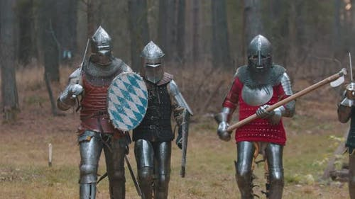 Four Men Knightes Walking in the Row in the Forest in Full Armour Holding Different Weapons