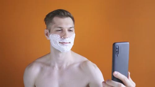 Cute Man with Shaving Foam on His Face Before Shaving His Stubble, He Makes a Video Call Using His