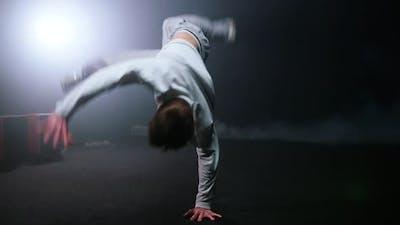 Young Man Performing Break Dancing Trick in Dark Studio