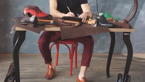 Footwear Designer Sitting at the Table and Drawing Model