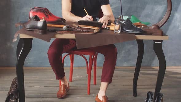 Thumbnail for Footwear Designer Sitting at the Table and Drawing Model