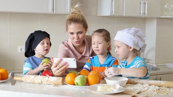 Thumbnail for Mother Shows Children How To Cook. Girl Looking a Recipe on a Mobile Phone