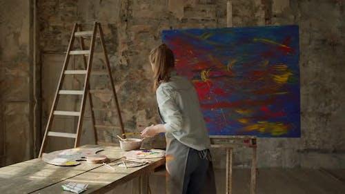 Woman Artist Holding Paint Brush on Large Canvas in Art Studio