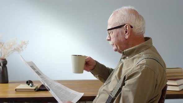 Thumbnail for Senior Man Drinking Coffee and Reading Newspaper