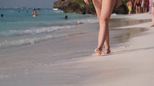 Legs of a Young Woman Walking By White Sand and Surf Waves of Ocean Shore