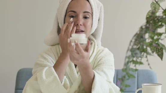 Thumbnail for Portrait of a Young Caucasian Girl in White Bathrobe and Hair Towel Applying Face Cream. Beautiful