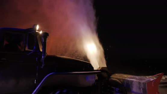 The Grader Removes Snow On The Road Outside The City At Night