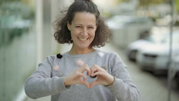 Thumbnail for Smiling Mature Woman Making Heart Shape with Hands