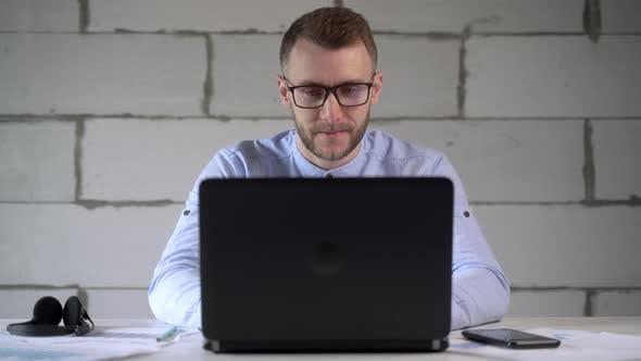 Geschäftsmann arbeitet mit Laptop und Geschäftskarten, während er zu Hause sitzt