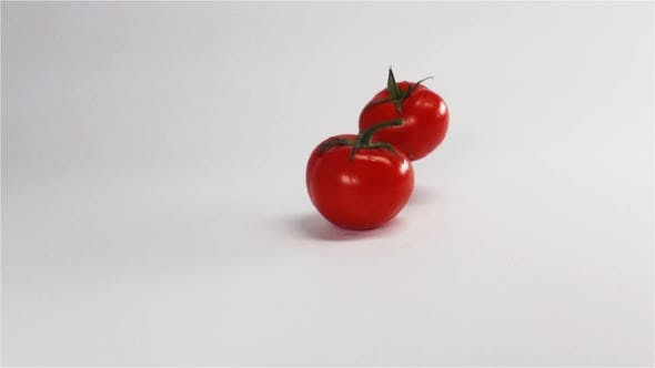 Thumbnail for Two Whole Wet Tomatoes Bouncing on White Surface