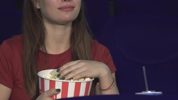 Thumbnail for The Young Lady Is Eating Popcorn During the Screening