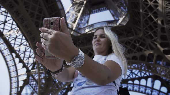 Cover Image for Happy Woman Taking Selfie Under Eiffel Tower