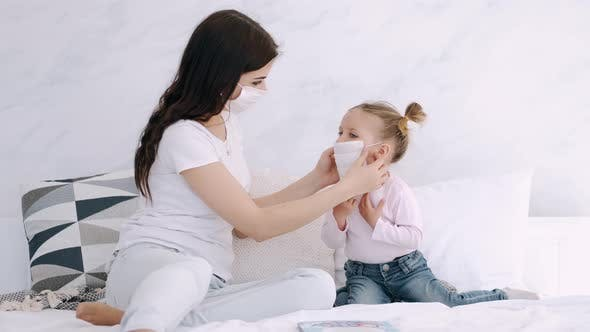 Thumbnail for Mother Is Putting a Mask on Daughter's Face