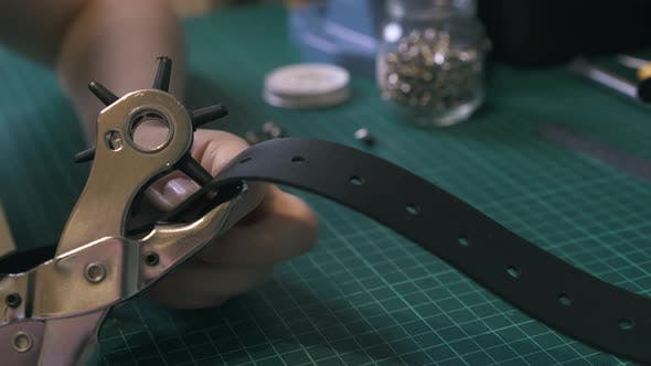 Tailor Makes Holes in Leather Belt with Silver Punch Pliers