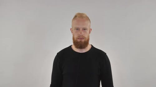 Red-haired Guy with a Beard Shows the Sign of Heavy Metal