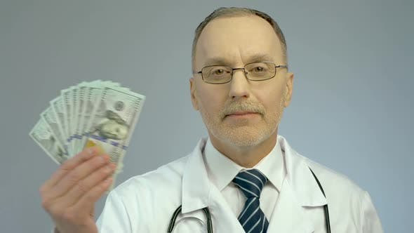 Cover Image for Doctor Holding Bundle of Dollars, Paid Medicine, Expensive Health Care Services