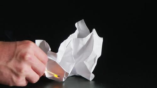 person lighting white ball of paper with match