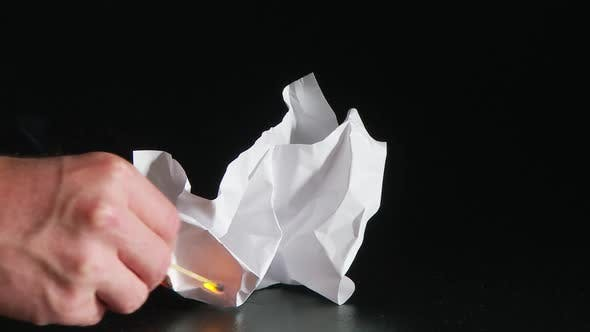 Thumbnail for person lighting white ball of paper with match
