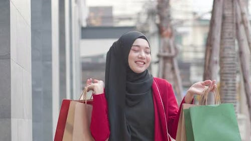 Muslim woman happy walking with carry many shopping bag