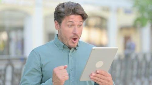 Man Celebrating on Tablet Outdoor