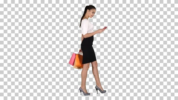 Thumbnail for Beautiful young woman using a mobile phone walking and holding