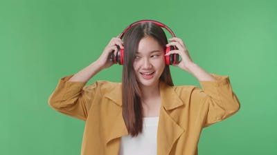 Asian Woman Listening To Music With Headphones And Dancing In The Green Screen Studio