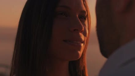 Thumbnail for Close up of a young woman looking at her boyfriend with love at sunset. Slow motion