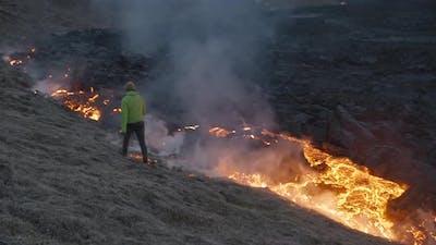 Man Walking Alongside Lava Flow From Erupting Fagradalsfjall Volcano