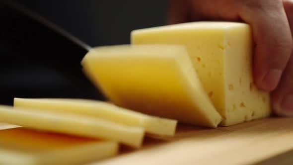 Mann schneidet ein Stück Käse auf Schneidebrett