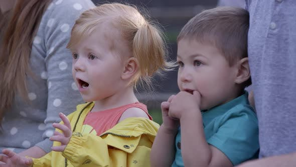 Thumbnail for Little boy and girl surprised as they are watching an event