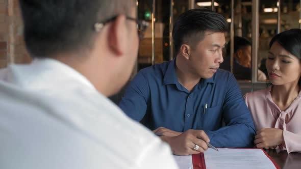Thumbnail for Mandanten diskutieren Vertrag mit Anwalt