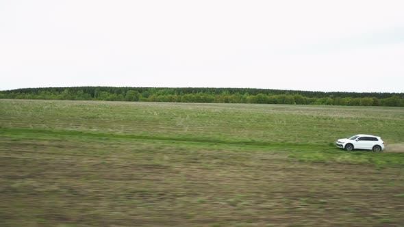 Thumbnail for Car Moving Through Green Field
