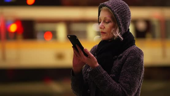 Thumbnail for Senior woman messaging on cellphone in downtown area, bus passing in background