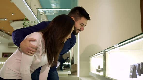 Thumbnail for Couple Looks at the Shopping Display with Jewelry at the Shop