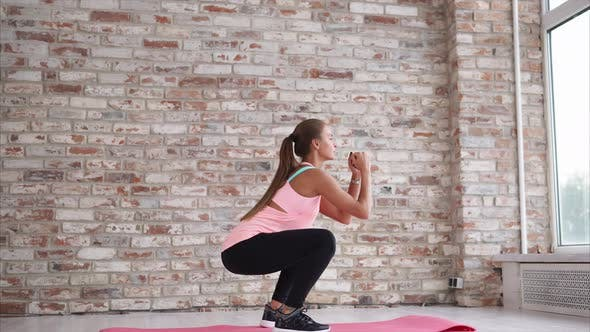 Young Woman Doing Active Situps to Strengthen the Feet in the Sports Center