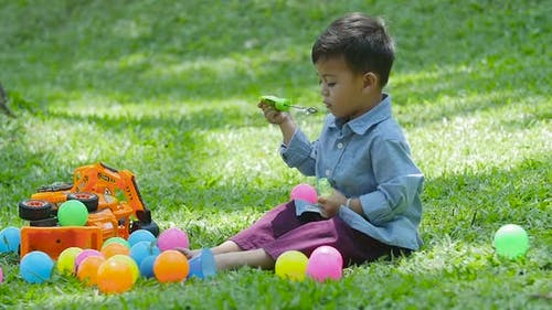 Little Boy Blowing Soap Bubbles on the Grass in the Park