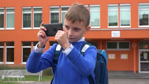 Thumbnail for A Young Boy Takes Pictures with a Smartphone - an Elementary School in the Background