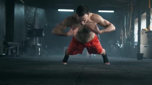 Athlet mit einem schönen Körper und einem nackten Torso beim Liegestümtraining auf dem Boden im Fitnessstudio