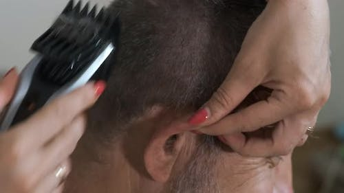 A woman cuts her husband's hair with an electric clipper  during quarantine.