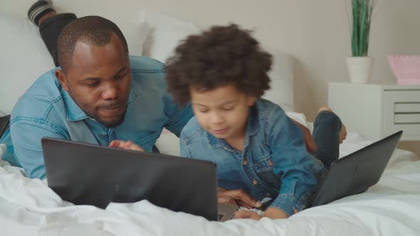 Thumbnail for Positive Father and Son Working on Laptop on Bed